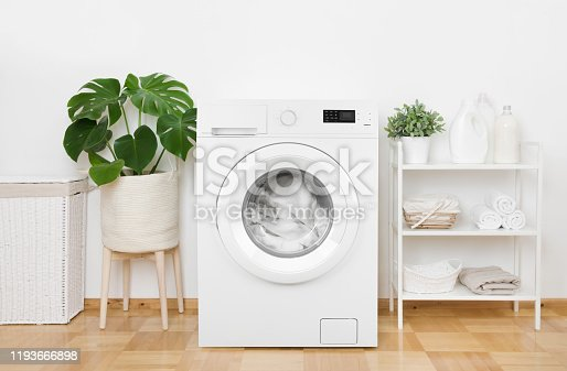 Interior of pastel colors laundry room with modern washing machine