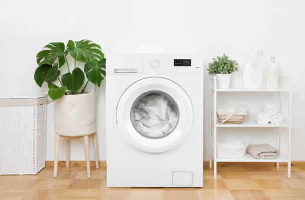Interior of pastel colors laundry room with modern washing machine stock photo