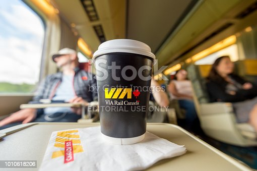 Interior of railcar on a ViaRail train on its way to Toronto, with a Via Rail Paper Coffee Cup in foreground