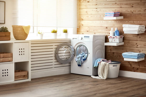 Interior of real laundry room with  washing machine at window at home stock photo