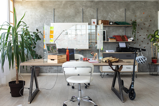 Interior of modern office with acrylic glass cough/spit protection wall against viruses on desk and whiteboard on wall