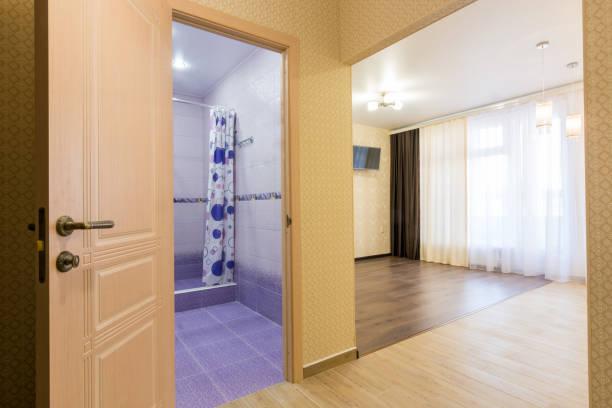 innere des studio-apartment, offene tür zum bad und zur ansicht des raumes - eingangshalle wohngebäude innenansicht stock-fotos und bilder