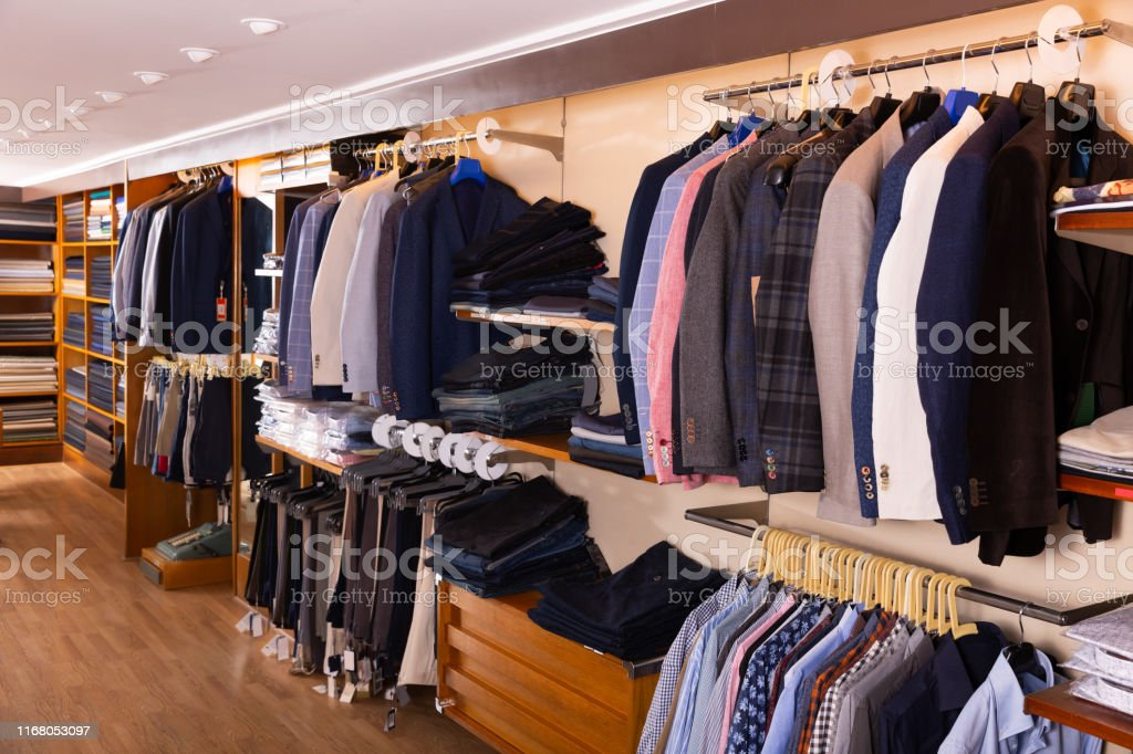 Interior of stylish men clothing store with variety of suit coats,...