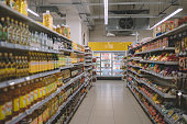 interior of supermarket full of grocery items in rows with shelf displayed