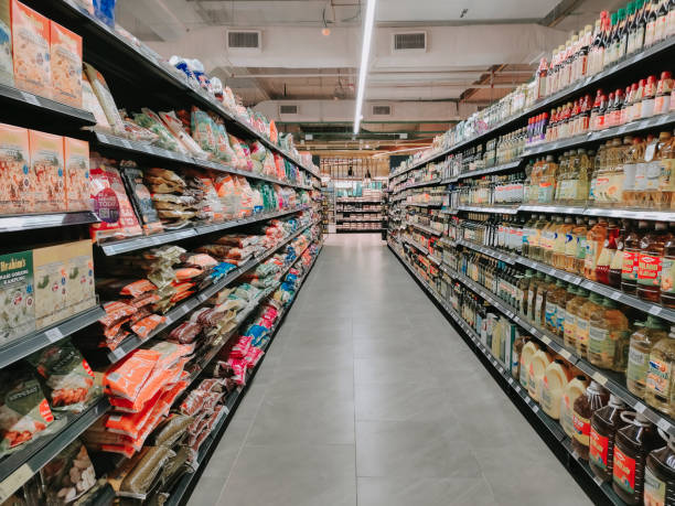 Interior of supermarket full of grocery items in rows with shelf displayed Interior of supermarket full of grocery items in rows with shelf displayed snack aisle stock pictures, royalty-free photos & images