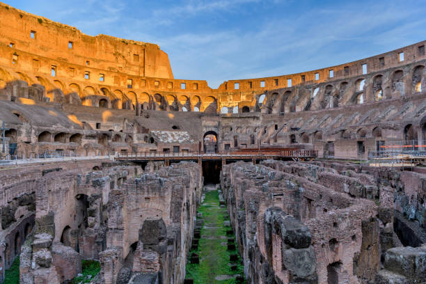 Interior of The Colosseum - A sunset view of the arena and hypogeum surrounded by ancient high walls inside of the Colosseum. Rome, Italy. stock photo
