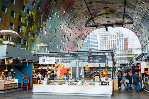 Interior of the Iconic Rotterdam Market Hall Rotterdam, The Netherlands - June 15, 2016: Food Stalls and Restaurants inside the Rotterdamse Markthal (Rotterdam Market hall). The Markthal, the first covered fresh market in the Netherlands, opened for business on 1 October 2014, after five years of construction. market hall stock pictures, royalty-free photos & images