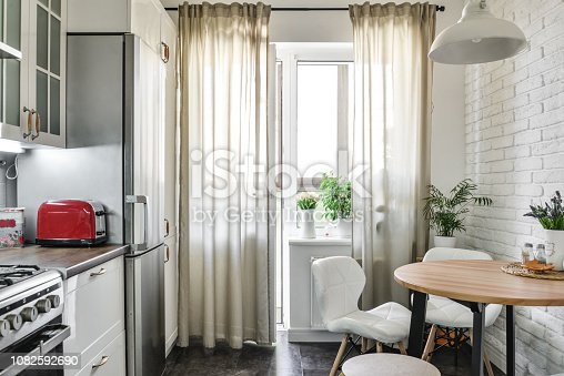 Interior of the kitchen in Scandinavian style with white furniture and a dining table.