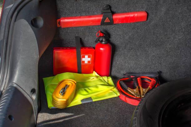 거기 있는 차 트렁크의 내부는 응급 처치 키트, 소화기, 경고 삼각형, 반사 조끼, 초보 케이블 및 견인 로프 - 응급 처치 뉴스 사진 이미지