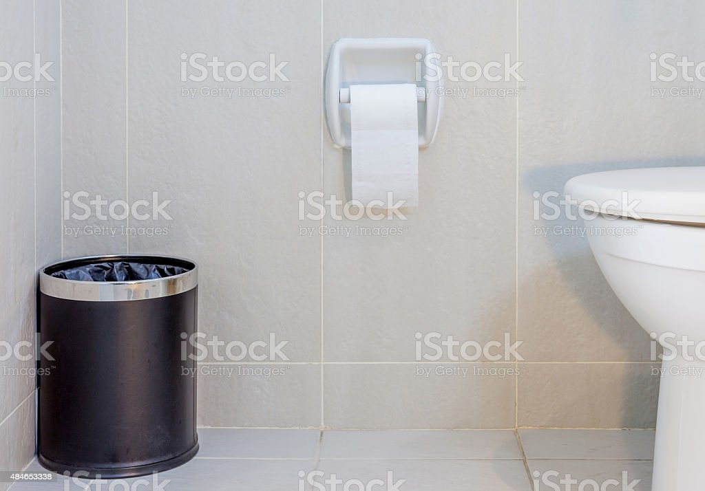 Interior of toilet seat, paper and trashcan in hygiene restroom. stock photo