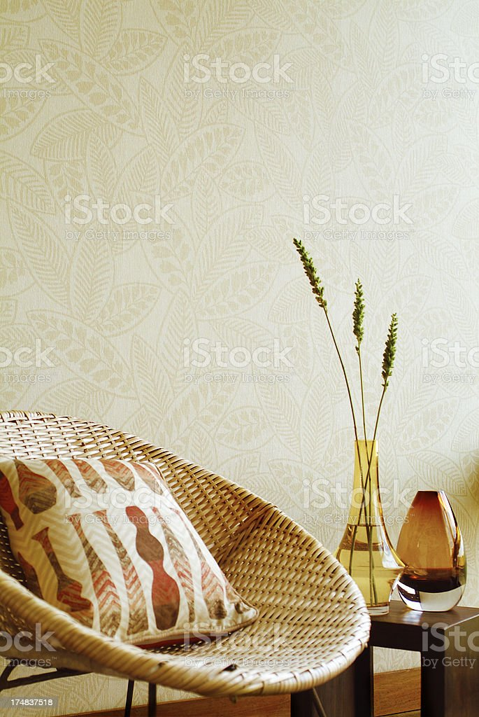 Interior of wicker chair against wall stock photo
