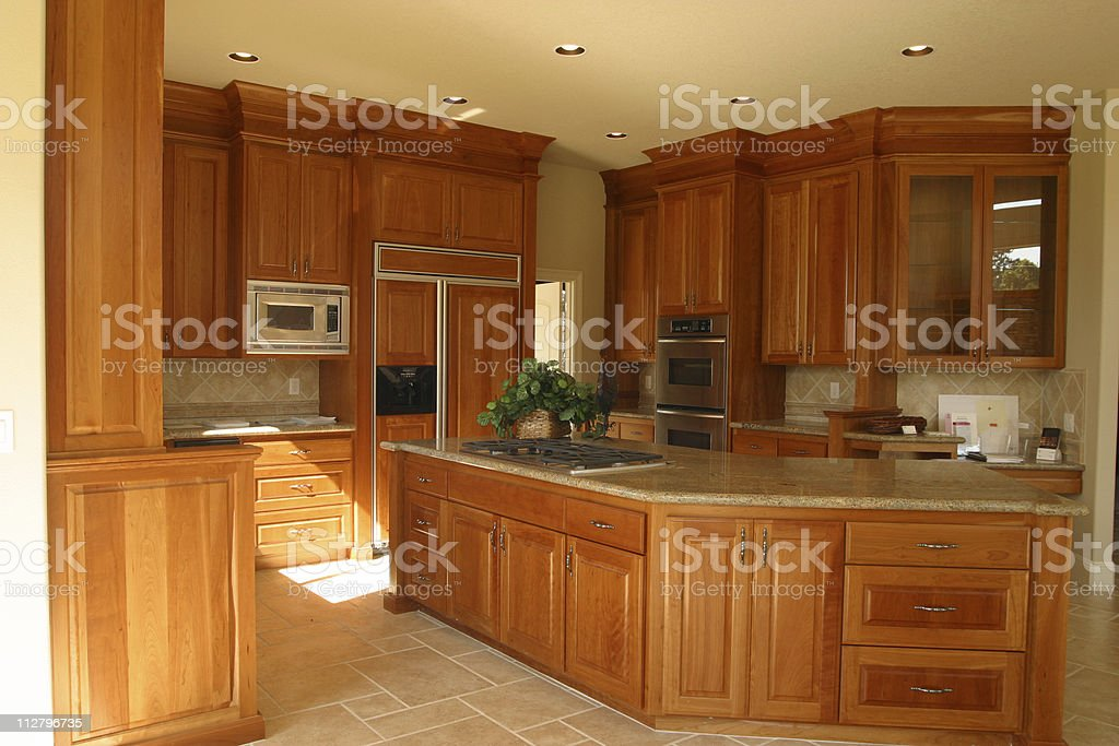 Interior of wood styled spacious Kitchen with tile floors royalty-free stock photo