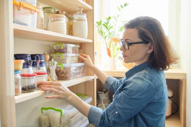Interior de despensa de madera con productos para cocinar. Mujer adulta tomando utensilios de cocina y comida de los estantes - foto de stock