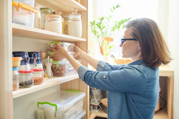Interior of wooden pantry with products for cooking. Adult woman taking kitchenware and food from the shelves Interior of wooden pantry with products for cooking. Adult woman taking kitchenware and food from the shelves. only mature women stock pictures, royalty-free photos & images