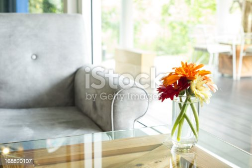Vase full of  colourful flowers on glass table with sofa at modern Cafe