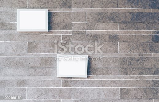 istock Interior poster mockup, White picture frame attached to a brown wall. 1090466152