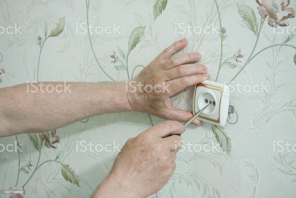 Interior repair. A professional electrician repairs socket on wall. stock photo