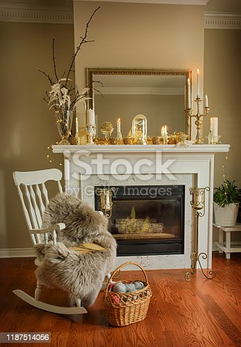 Interior room with elegant Christmas decoration on fireplace, chair  and basket with balls of yarn