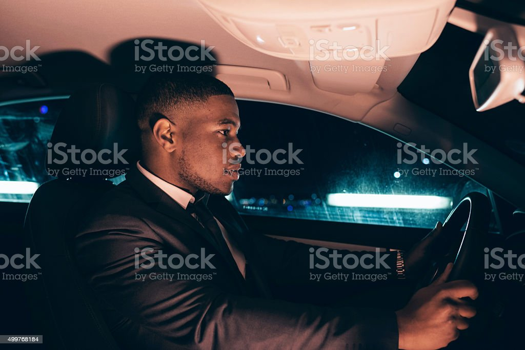 Interior shot of young man in suit driving car. stock photo