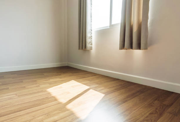 Interior space, empty room, laminate wooden floor with opened window receiving sunlight in the morning stock photo