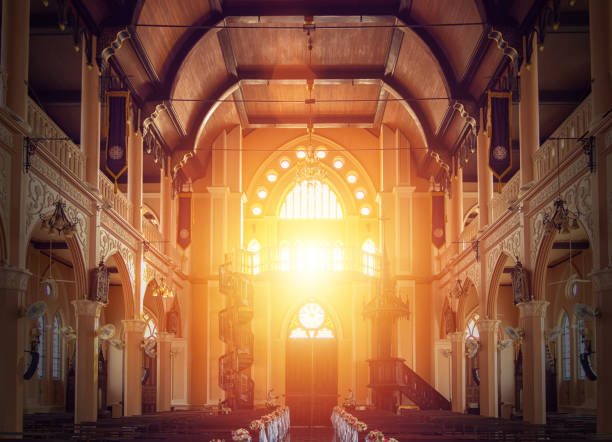 interior view of empty church with wooden bench decorated with flower bouquet, sunlight through church stained glass window interior view of empty church with wooden bench decorated with flower bouquet, sunlight through church stained glass window place of worship stock pictures, royalty-free photos & images