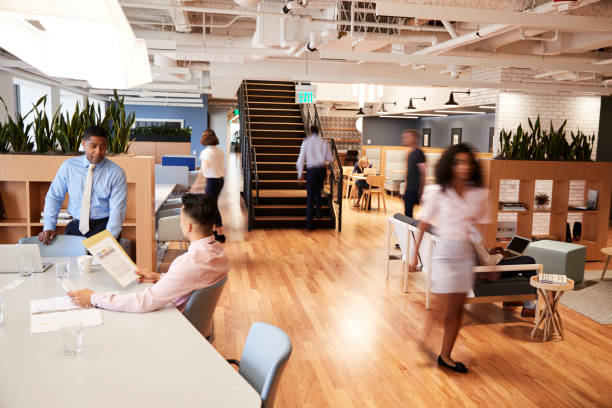 Interior View Of Modern Open Plan Office With Blurred Businessmen And Businesswomen Interior View Of Modern Open Plan Office With Blurred Businessmen And Businesswomen long exposure stock pictures, royalty-free photos & images