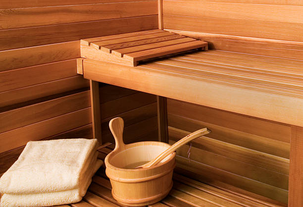 Interior View of Sauna Bath Close-up shot of inside of sauna showing bench, towels and pail. sauna stock pictures, royalty-free photos & images