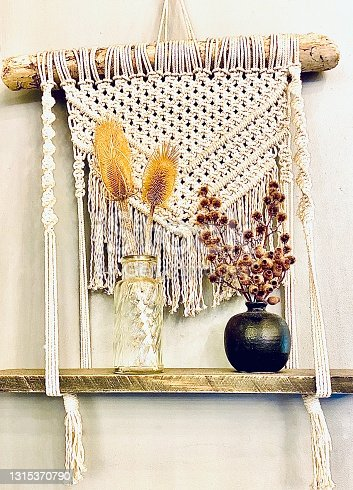 Vertical still life interior wall display of handmade macrame shelf with wood and vases of dried flowers