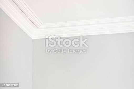 Close-up of the corner of a room meeting the ceiling with a simple plaster cornice.