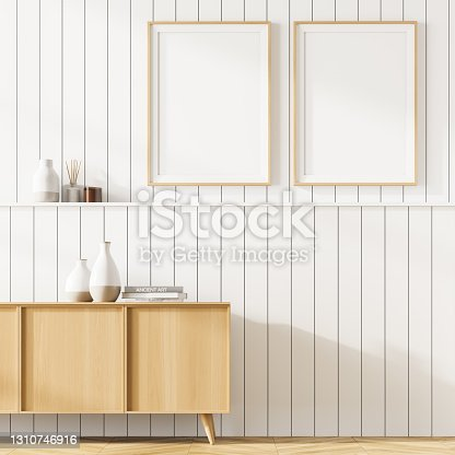 Living room interior with a cosy wooden cabinet. White wall is decorated with two vertical poster. Minimalistic designer decision represents modern way of decoration. Mock up. 3d rendering