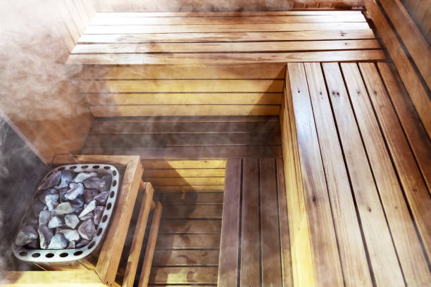 Interior wooden sauna room Interior of small home Finnish wooden sauna. Infrared sauna. Cedar bath. beautiful nature interior home finnish sauna room background. inside the sauna. Hot stones in the bath. sauna stock pictures, royalty-free photos & images