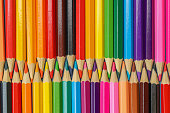 Close up row of interlocking colored pencils in a rainbow of colors