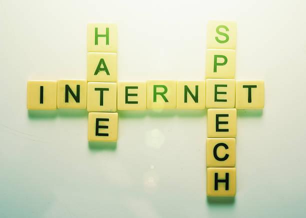 Interlocking game tiles spell out Internet Hate Speech stock photo