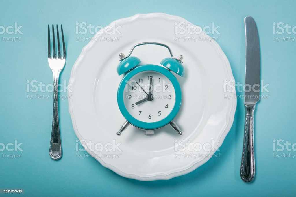 Intermittent fastin concept - empty plate on blue background stock photo