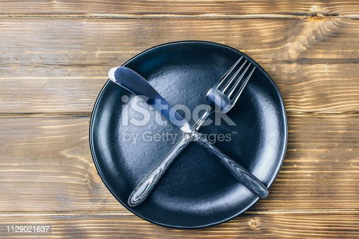 Intermittent fasting concept with knife and fork showing cross symbol on black plate, top view