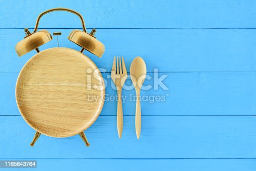 istock Intermittent fasting, diet and weight loss concept : Clock shaped wood dish, spoon and fork. Eco-friendly plate / kitchen utensil as alarm clock with ringing bell, depict alert or reminder time to eat 1165643764