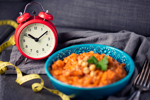 Losing weight with intermittent fasting gets more and more popular, here showed with a clock and traditional, vegan Chana Alu Masala, an indian dish
