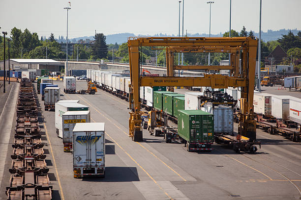 Intermodal containers being moved from railcars to trailers. stock photo