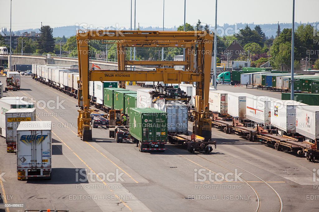 Intermodal freight conainers being moved with a gantry crane. stock photo