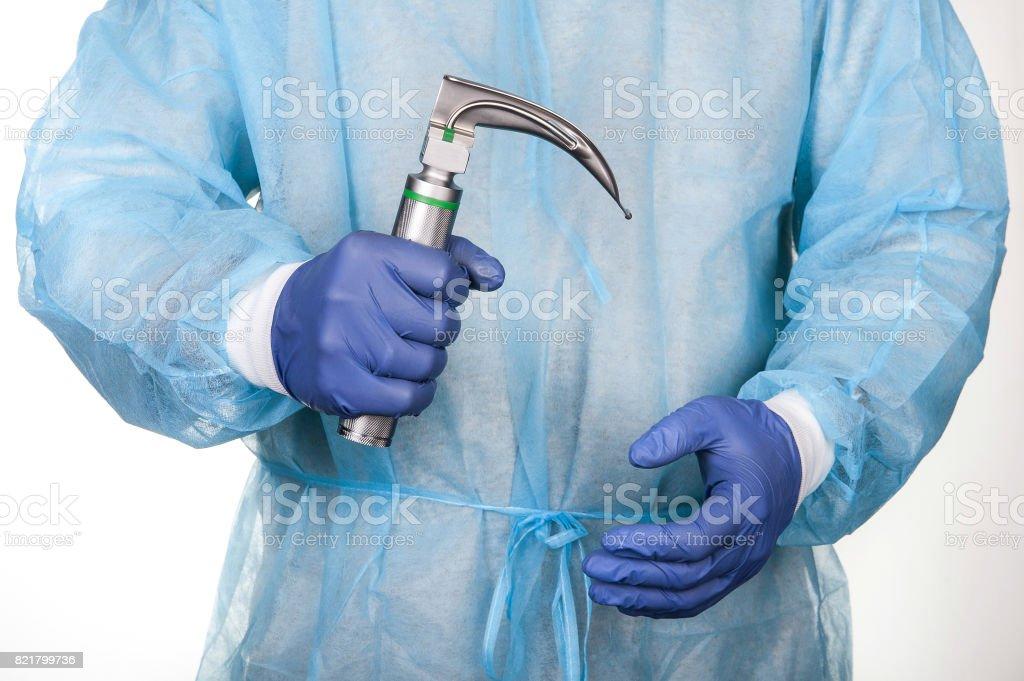 Intern holding laryngoscope, isolated on white background stock photo