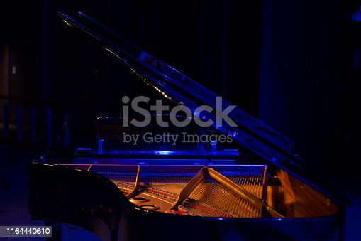 Internal details of a baby grand piano in blue and purple light on stage prior to a performance