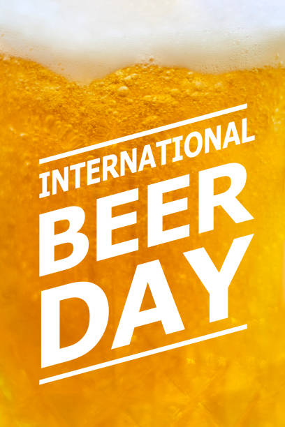 International Beer day Close-up view of beer glass with text overlay on it - International beer day. Glass of cold light beer with bubble froth in glass. Drink alcohol, celebration, party, holiday concepts muziekfestival stock pictures, royalty-free photos & images