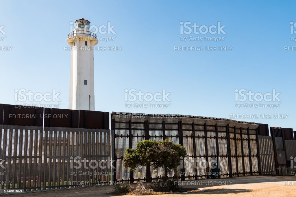 People communicate through the international border wall between San...
