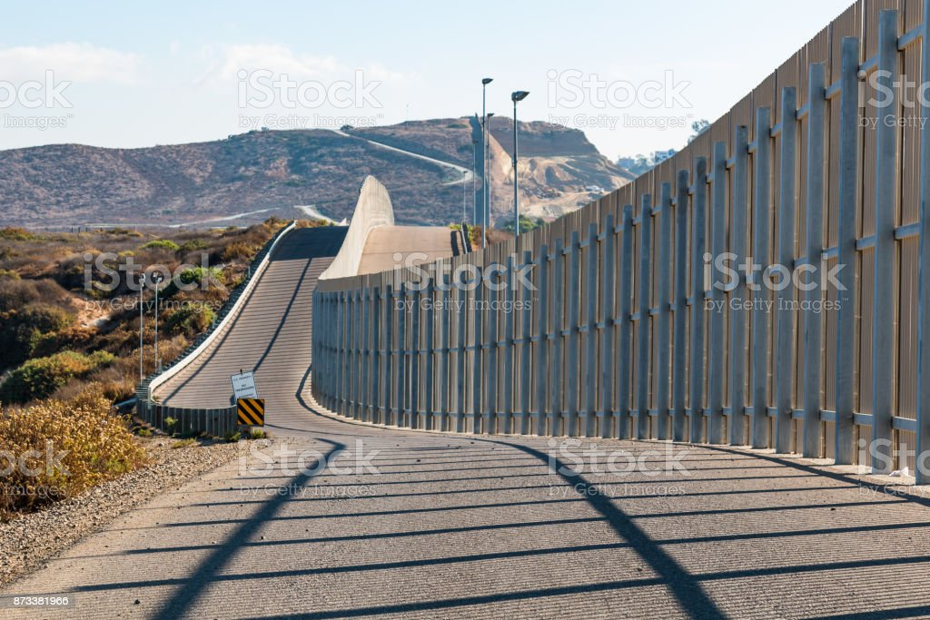 International Border Wall Between San Diego and Tijuana Extending into Distant Hills The international border wall between San Diego, California and Tijuana, Mexico, as it begins its journey from the Pacific coast and travels over nearby hills. Barricade Stock Photo