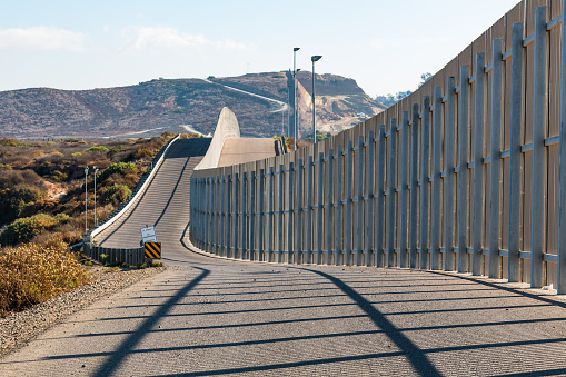 International Border Wall Between San Diego And Tijuana Extending Into Distant Hills Stock Photo - Download Image Now