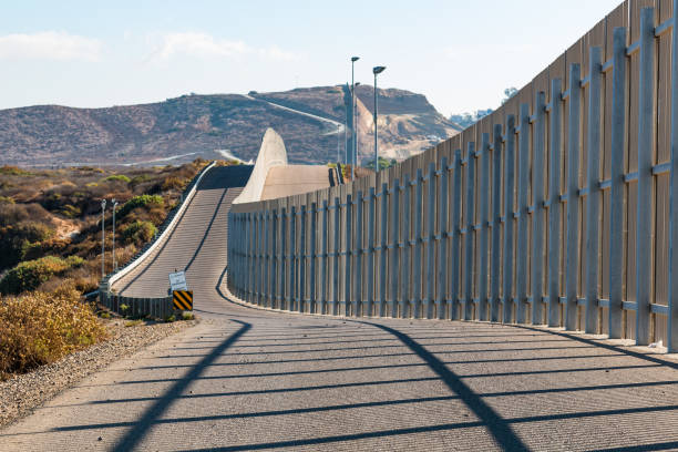 International Border Wall Between San Diego and Tijuana Extending into Distant Hills The international border wall between San Diego, California and Tijuana, Mexico, as it begins its journey from the Pacific coast and travels over nearby hills. international border barrier stock pictures, royalty-free photos & images