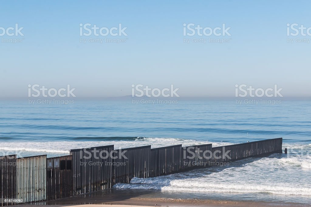 International Border Wall Extending to Pacific Ocean stock photo
