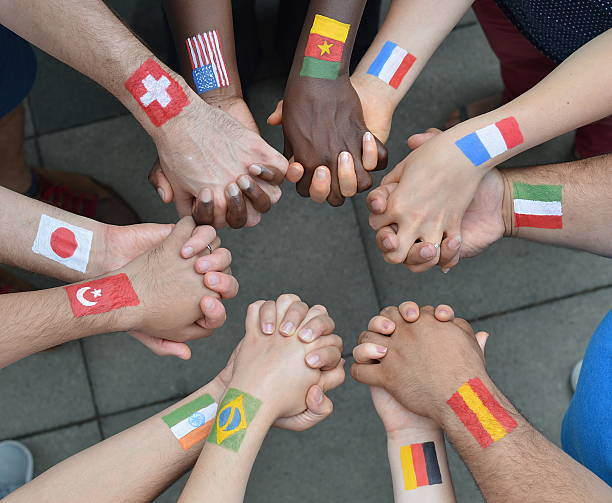 International brothers and sisters in a circle International brothers and sisters standing in a circle together and holding hands as a symbol for peace and the world community customs stock pictures, royalty-free photos & images