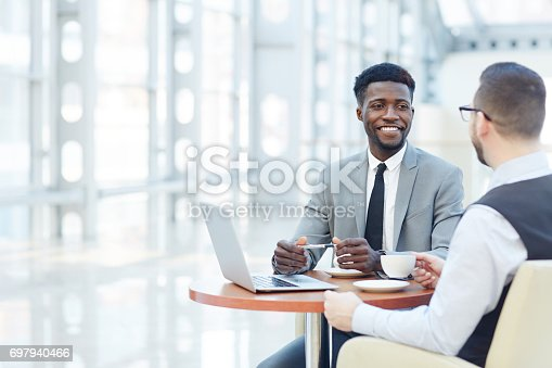 istock Portrait of successful African-American businessman smiling during meeting with colleague at coffee break 697940466