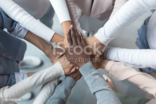 Top view of international business team showing cooperation with putting their hands together on top of each other